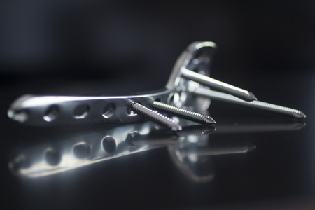 Orthopedic implant surgery Traumatology silver colored titanium plate and screws in semi silhouette Against plain black studio background. Horizontal Close-up macro photograph in gray tones with reflection.