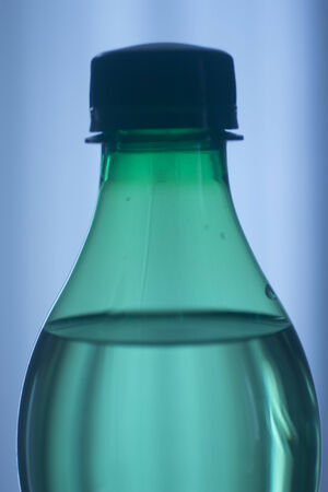 Isolated plastic water bottle on a plain blue studio background close-up photo.