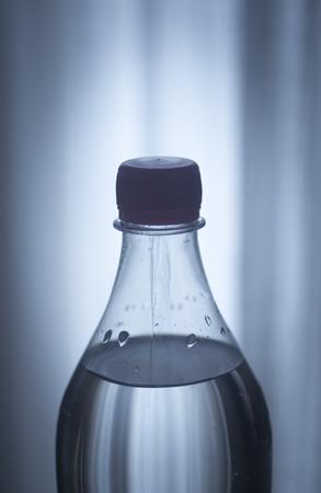 分離の青いプラスチックのソーダ レモネード清涼飲料ボトル プレーン ブルー スタジオ背景のクローズ アップ写真。