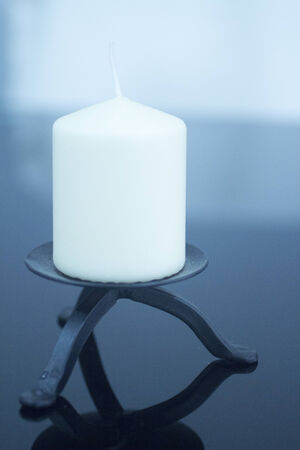 man made object: One large white candle on black metal decorative dish on plain studio blue background with reflection.