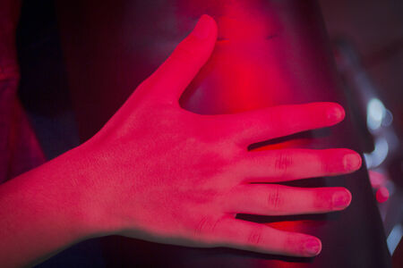 Hand of injured patient receiving treamente under red rehabilitation phisiotherapy hospital clinic heat lamp.