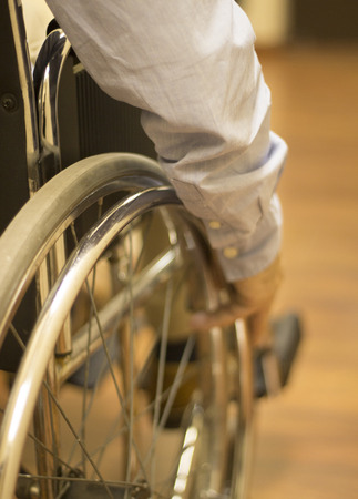 warm shirt: Man sitting in wheel chair wearing blue shirt pushing wheel to move himself forward in hospital clinic. Color digital photo in warm tones shot from behind with shallow depth of focus. Stock Photo