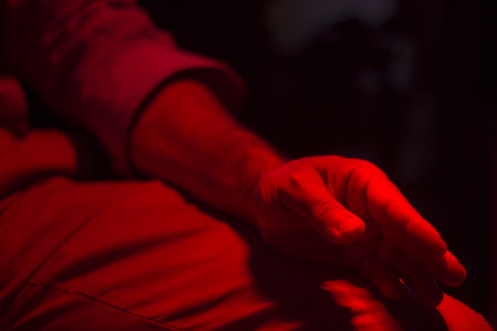 Hand of injured patient receiving treament under red rehabilitation hospital clinic heat lamp. Stock Photo