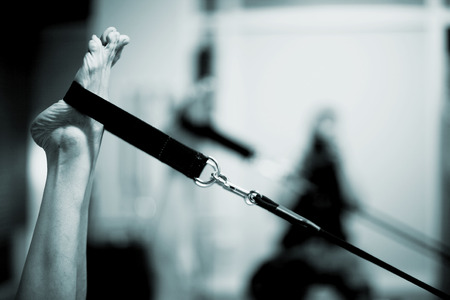 Feet of a young woman realising an exercise of pilates on a pilates machine strap and cord in a healthclub gym specialized training room. Black and white monochrome photo in blue tone. Standard-Bild