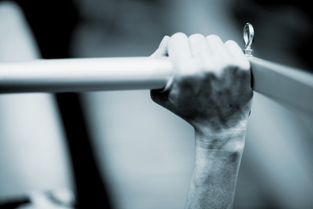 Hand of a young woman realising an exercise of pilates on a pilates machine bar in a healthclub gym specialized training room. Black and white monochrome photo in blue tone. Stock Photo