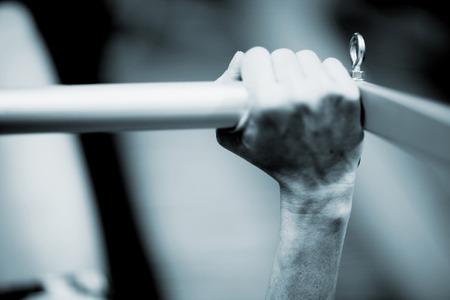 healthclub 체육관 전문 교육 실에서 필라테스 기계 바에서 필라테스의 운동을 실현하는 젊은 여자의 손입니다. 블루 톤의 흑백 흑백 사진.