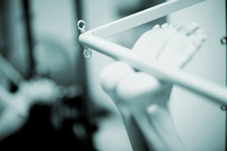 Piedi di una giovane donna di realizzare un esercizio di pilates su una barra macchina di pilates in una sala di formazione healthclub palestra specializzata. In bianco e nero in bianco e nero foto in tonalità blu. Archivio Fotografico - 34222295