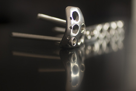 titanium: Traumatology orthopedic surgery implant titanium plate and silver color screws in semi silhouette against plain black studio background. Close-up macro horizontal photograph in grey tones with reflection.