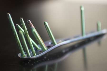 titanium: Traumatology orthopedic surgery implant titanium plate and green screws in semi silhouette against plain studio background. Close-up macro horizontal photograph in grey tones with reflection. Stock Photo