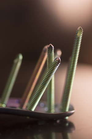 titanium: Traumatology orthopedic surgery implant titanium plate and green screws in semi silhouette against plain studio background. Close-up macro vertical photograph in purple tones. Stock Photo