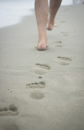 Vertical photo of feet of man and footprints on sand of beach on grey cold day with sea defocused in background. Taken in Viareggio in Tuscany Italy on the Mediteranean sea coast. photo