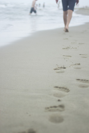 swimming shorts: Vertical photo of legs of man wearing swimming shorts and footprints on sand of beach on grey cold day with sea and bathers defocused in background. Taken in Viareggio in Tuscany Italy on the Mediteranean sea coast. Stock Photo