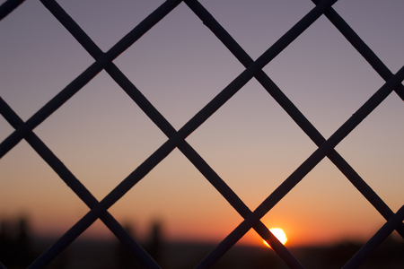 confined space: Horizontal color digital photo of setting evening sun and red and blue sky shining through a metal wire mesh fence in silhouette at dusk in dark tones with bokeh blur shallow depth of focus defocused landscape background.