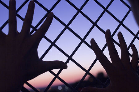confined space: Color digital photo of setting evening sun and red and blue sky shining through a metal wire mesh fence with two human hands of a man against the fence with outstretched fingers in silhouette at dusk in dark tones with bokeh blur shallow depth of focus. Stock Photo
