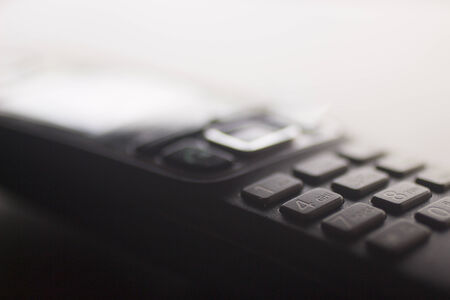 Close-up macro photo of a hands wifi free domestic home or work office fixed line telephone keypad. Artistic color digital photo with shallow depth of focus.