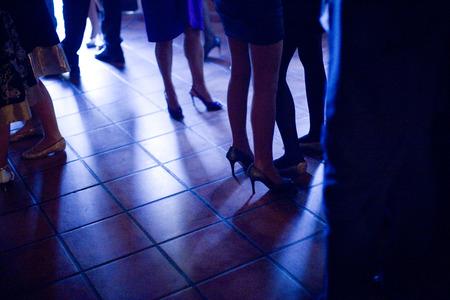 Las piernas de las damas jóvenes vistiendo zapatos de tacones altos y vestidos de coctel cortos personas de pie en el piso de baldosas de brillante en el banquete de boda evento social en Madrid España. Noche fotografía color de tono azul.