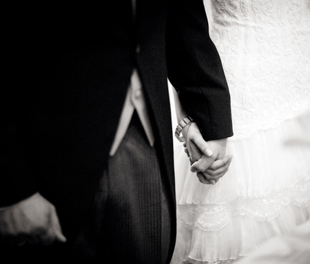 Black and white artistic digital rectangular horizontal photo of the bride wearing white wedding dress holding hands with the bridegroom wearing long jacket dark morning suit during church wedding marriage ceremony in Madrid Spain. photo