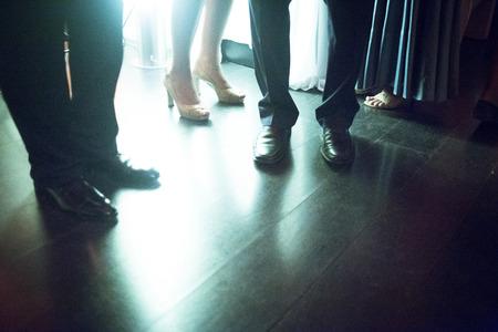 Las piernas de los hombres y señora que lleva en pie en el piso de baldosas brillante en evento social fiesta matrimonio boda en Madrid España. Verde tarde noche fotografía color de tono.