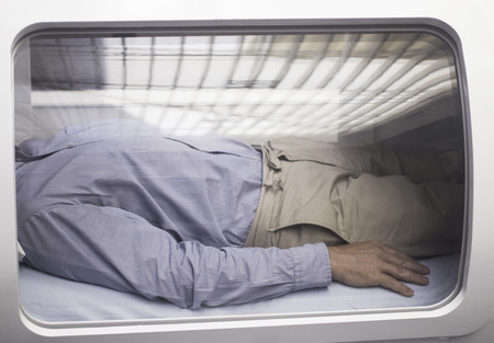 Male patient aged 45-55 wearing blue shirt and beige chino trousers lying down in hyperbaric oxygen chamber receiving Hyperbaric Oxygen Therapy (HBOT) specialised medical treatment for injuries with reflection on glass.
