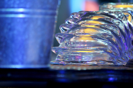 cheroot: Color photo of a group of upturned clear glass cigarette ash trays sparkling in the light