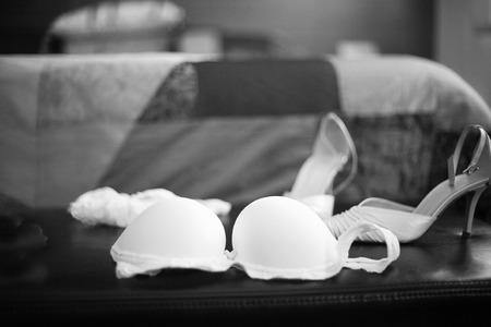 garter belt: Wedding bridal garter belt, bra lingerie and white shoes in Madrid Spain. Black and white photo with shallow depth of focus.
