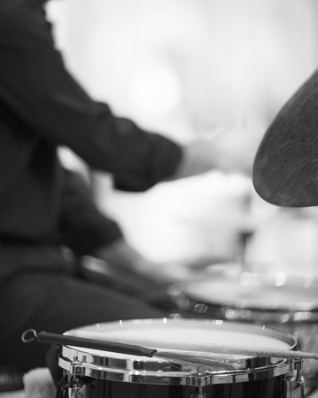 Black and white artistic digital rectangular vertical photo of drumsticks on drum and drummer playing drumset in wedding party reception in Barcelona Spain. Shallow depth of with background out of focus. photo