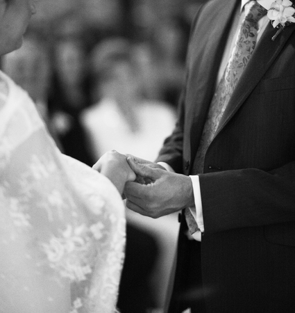 Black and white artistic digital rectangular horizontal photo of hand of bridegroom in dark long morning suit and white shirt with cufflinks in church religious wedding marriage ceremony holding hands to exchange wedding rings with the bride in white long photo
