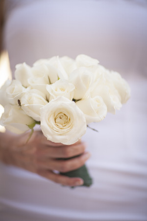 Bride in white wedding dress holding bouquet of roses flowers close-up photo. photo
