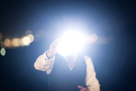 Color artistic digital rectangular horizontal photo of hand of man in dark suit and white shirt in night time wedding banquet marriage party holding camera taking a photo with flash in Barcelona Spain. Shallow depth of with background out of focus.