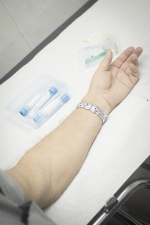 nurse gloves: Close-up color photo of a female hospital clinic nurse wearing sterile blue gloves and senior male patient aged 65-70 giving a blood donation sample from the interior of his elbow resting arm on sterile blue white defocused background.