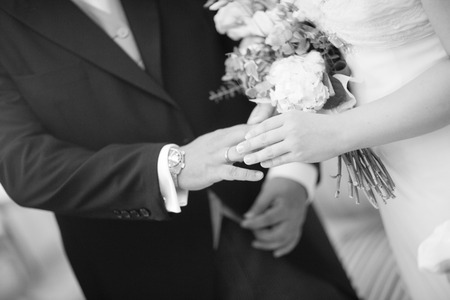 Black and white artistic digital photo of bridegroom in dark suit and white shirt in church religious wedding marriage ceremony holding hands with the bride in white long wedding bridal dress. Shallow depth of with background out of focus.