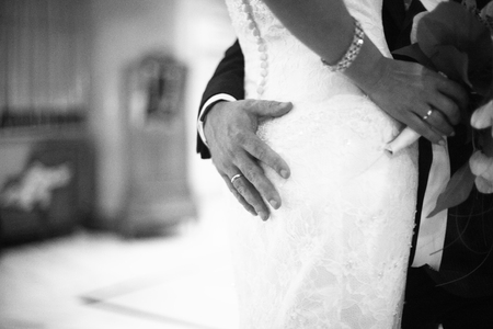 holding close: Black and white artistic digital photo of bridegroom in dark suit in wedding marriage event holding hands with the bride in white long wedding bridal dress. Shallow depth of with background out of focus.