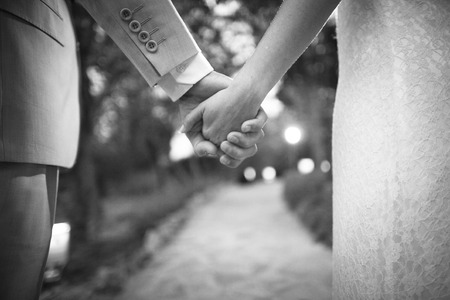 holding close: Black and white artistic digital photo of bridegroom in dark suit and white shirt in wedding marriage holding hands with the bride in white long wedding bridal dress. Shallow depth of with background out of focus.