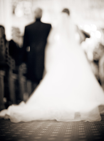 Bride in white dress and father walking down the aisle in catholic religious church defocused.