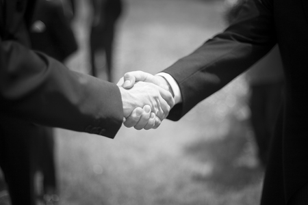 Men shaking hands in wedding reception party black and white photo. photo