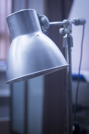 Physiotherapy heat medical rehabilitation lamp in hospital clinic in artistic tones.