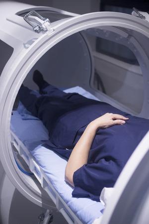Vrouwelijke patiënt 45-55 jaar dragen bloem jurk liggend in hyperbare zuurstof kamer ontvangen Hyperbare zuurstoftherapie (HBOT) gespecialiseerde medische behandeling voor verwondingen.