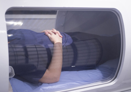 specialised: Female patient aged 45-55 wearing flower dress lying down in hyperbaric oxygen chamber receiving Hyperbaric Oxygen Therapy (HBOT) specialised medical treatment for injuries.