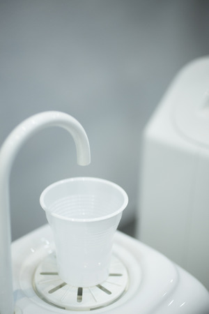 pip: Dentists water cup tap pip filler in dental clinic in artistic blue purple white tones.