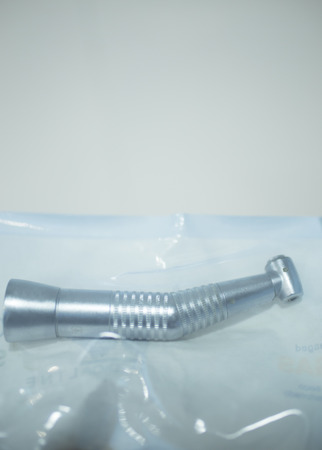 dentist drill: Dental instrumenation dentist drill and cleaning tool in denstists surgery clinic vertical color photo in hygiene plastic wrap ready for use. Stock Photo