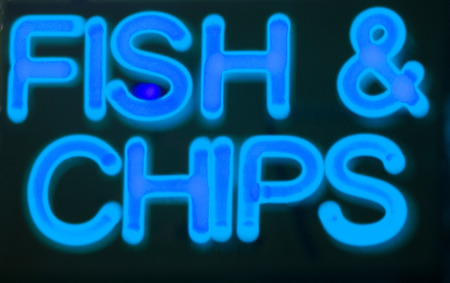 neon fish: Fish and chips restaurant neon sign at night in street photo.