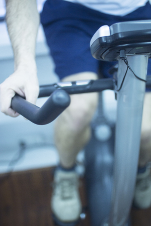 Young man on exercise bicycle in physiotherapy gym fitness center clinic.