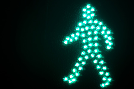 to light: Green man go pedestrian traffic light photo at night on black background.