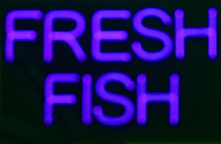 neon fish: Fresh fish  neon sign at night in street photo.