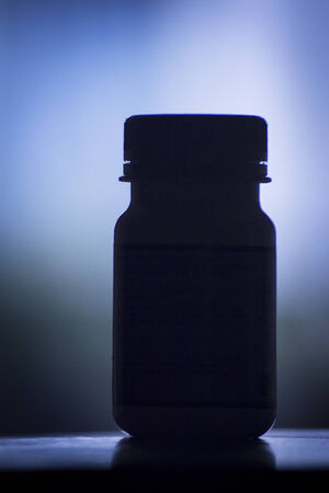 vitamin pill: Vitamin pill bottle silhouette photo.