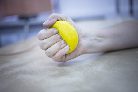 rheumatoid: Female patient with physical injury and Rheumatoid arthritis squeezing physiotherapy ball with hand in hospital clinic resting on bed.