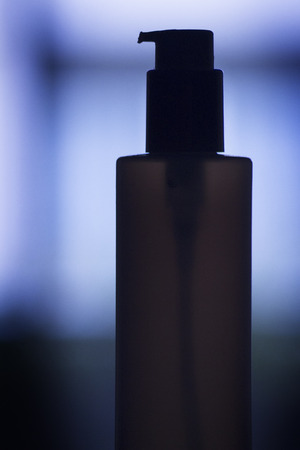 aftershave: Cosmetics container dispenser blue silhouette photograph.