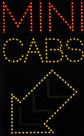 Mini cabs taxi with arrow neon sign light at night in street photo. photo