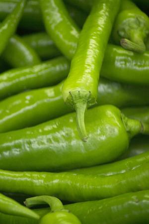 grocers: Green peppers vegetables on sale in supermarket grocers shop on display.