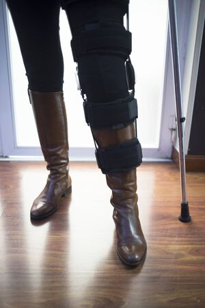 Woman in black jeans and leather boots walking on aluminium metal crutches in hospital clinic. photo